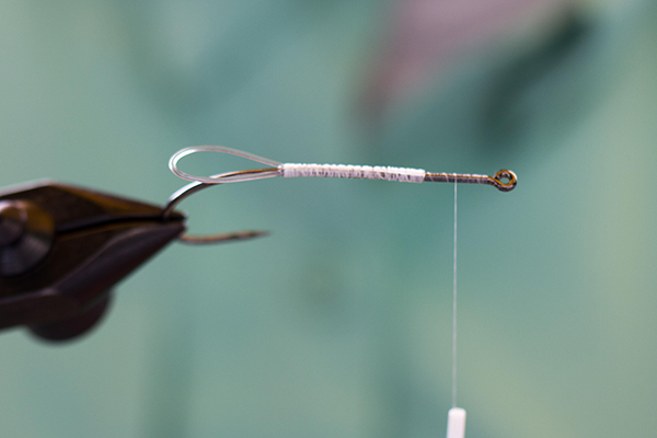 Ein Hard Mono wird auf dem Hakenschenkel in Form einer Schlaufe eingebunden. Es verhindert, dass sich später das Hasenfell beim Fischen ständig im Hakenbogen hängen bleibt.